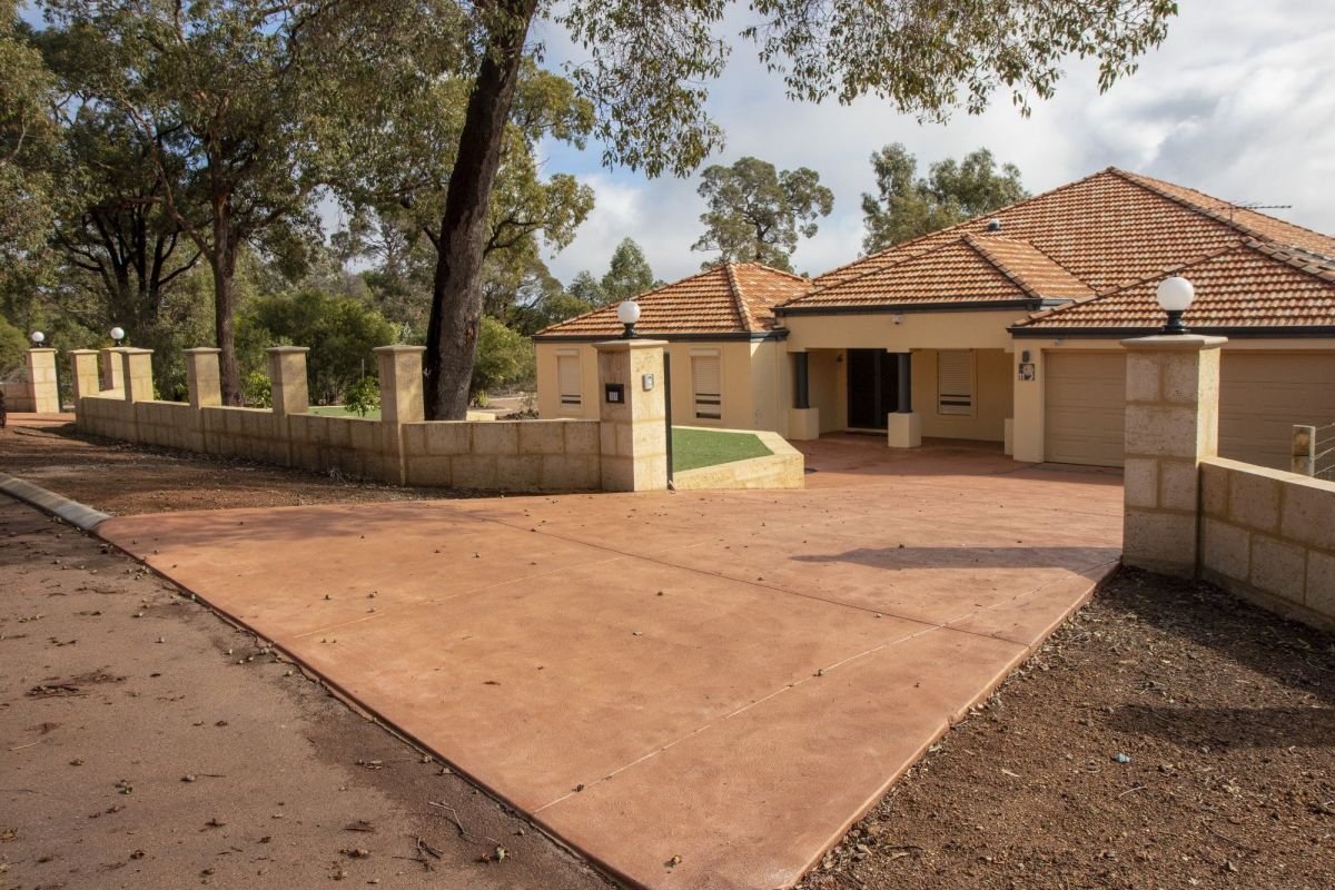 Coloured Conrete Driveway with Limestone Wall